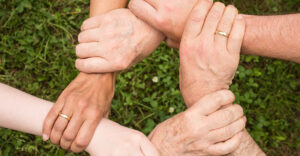 Five people joining their hands to form a circle.