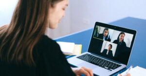 The home page shows a digital illustration of paper boats floating over a water body. Scrolling down the page shows 3 photos. The first photo shows a woman in formal attire seated in front of a table with a laptop attending a video conference. The second photo shows a woman in formal attire seated on a chair being recorded on a video camera. The third photo shows close-up of a woman's eye and nose surrounded by a digital space.